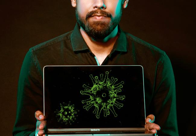 hombre sosteniendo un ordenador con virus